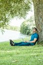 Young man with laptop outdoor sitting on the grass Royalty Free Stock Photo