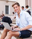Young man with laptop outdoors handsome sitting on a steps Royalty Free Stock Photography
