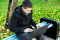 Young man laptop sitting bench autumn park Royalty Free Stock Photo