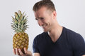 Young man laughing holding a pineapple Royalty Free Stock Photo