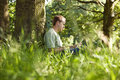 A young man leaning against a tree, using a laptop Royalty Free Stock Photo