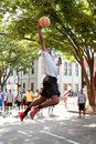 Young man leaps to dunk basketball during outdoor street tournament athens ga usa august a slam the in an impromptu competition in Royalty Free Stock Photo
