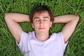 Young man lies on grass head on hands closed eyes Royalty Free Stock Photo