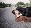 Young man lies on the old suitcase road Stock Photo