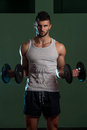 Young Man Lifting Dumbbell In Gym Royalty Free Stock Photo