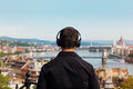 Young man listening music back view with Budapest Royalty Free Stock Photo