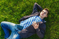 Young man listening music from smart phone on the grass in the park.
