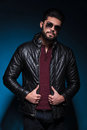 Young man with long beard is holding his leather jacket and looks at the camera Stock Photography