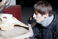 Young man looking at animal skull on dark background Royalty Free Stock Photos