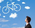 Young man looking at bicycle clouds on blue sky business Stock Image