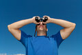 Young man looking with binoculars Royalty Free Stock Images