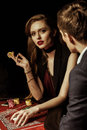 Young man looking at gorgeous woman with poker chip in casino Royalty Free Stock Photo