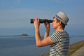 Young man is looking through the spyglass at the sea a in hat and striped t shirt blue sky island Stock Photography