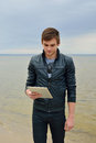 The young man is looking on a tablet in front of sea leather jacket Stock Photos