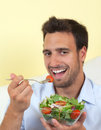 Young man loves vegetarian food smiling eats a salat beacuse he healthy Royalty Free Stock Photos