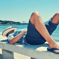 Young man lying down in a street bench near the sea caucasian with straw hat on his face Royalty Free Stock Photo
