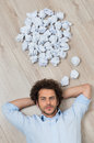 Young man lying on floor with crumpled papers over s head Stock Image