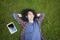 Young man lying on grass and listening music Royalty Free Stock Photo