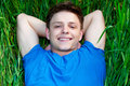 Young man lying on green field Royalty Free Stock Images