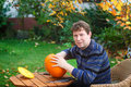 Young man making halloween pumpkin jack o lantern for in autumn garden Stock Images