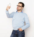Young man making photo of himself life style tehnology and people concept a in shirt holding mobile phone and while standing Royalty Free Stock Photo
