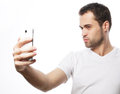 Young man making photo of himself life style tehnology and people concept a in shirt holding mobile phone and while standing Royalty Free Stock Photos
