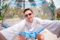 Young man making selfie relaxing at hammock Royalty Free Stock Photo