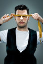 Young Man with a Metre Rule in Front of His Face Royalty Free Stock Photo