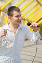 Young man with microphone Stock Images