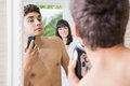 Young man in mirror shaving with electric shaver Royalty Free Stock Photo
