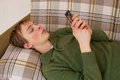 Young man with the mobile phone lying down on sofa sending text message on Stock Images