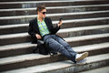 Young man with a mobile phone sitting on the steps Royalty Free Stock Photo