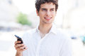Young man with mobile phone standing outdoors Stock Photos