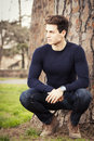 Young man model in a park under a tree Royalty Free Stock Photo