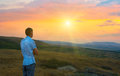 Young man in the mountains at sunset Stock Image