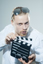 Young man with movie clapper in white shirt Royalty Free Stock Photography
