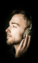 Young man musing as he listens to music attractive bearded his on stereo headphones looking off the left in profile with a Stock Photos