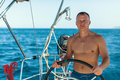 Young man with naked body at the helm of a sailing yacht boat. Sport. Royalty Free Stock Photo