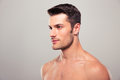 Young man with nude torso looking away over gray background Royalty Free Stock Images