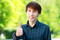 Young man outdoors smiling with thumbs up outdoor Royalty Free Stock Photo