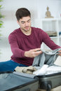 Young man packing bag and preparing for traveling Royalty Free Stock Photo