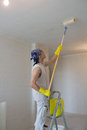Young man painting ceiling with painting roller worker Royalty Free Stock Image