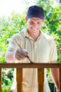 Young man painting wooden fence Stock Images