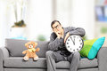 Young man in pajamas holding a clock seated on couch with teddy big wall bear next to him at home Stock Photos