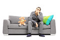 Young man in pajamas in thoughts seated on sofa with teddy bear deep a next to him isolated white background Stock Images