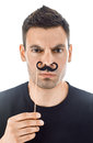 Young man with paper moustaches making faces isolated on white b Royalty Free Stock Photo