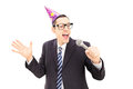 Young man with party hat singing isolated on white background Royalty Free Stock Image