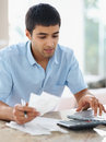 Young man paying bills using laptop at home Royalty Free Stock Photos