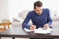 Young man paying his bills at home in the living room Royalty Free Stock Image