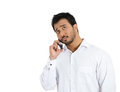 Young man on phone having a serious thought on the conversation closeup portrait of student agent corporate employee deal maker Royalty Free Stock Photos